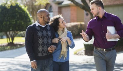 An African American couple walking on a residential street, with a young man holding a folder.  He is a real estate agent, talking to them about the houses in the neighborhood.